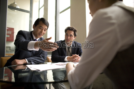 two young adult businessmen sitting with