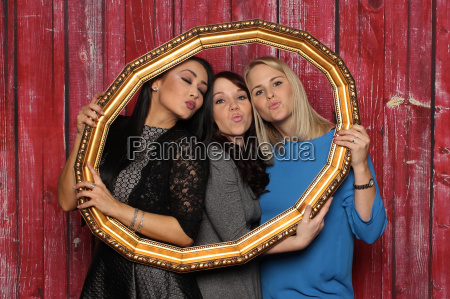 three women look through a picture