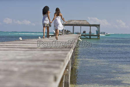 two young adult girls running along