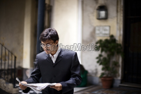 a man is carefully reading papers