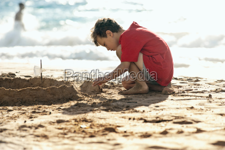 young boy building a sandcastle on