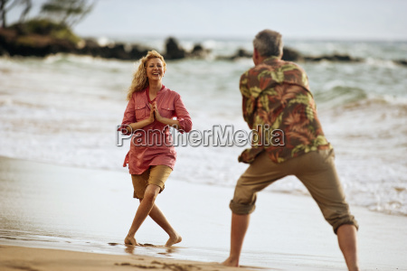 couple on the beach playfully taking