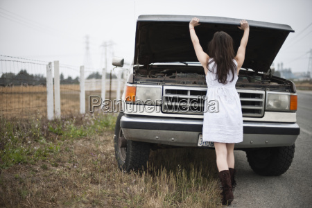 young woman inspecting the engine of