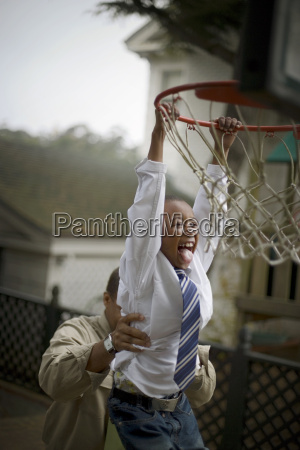 laughing boy hanging from a basketball