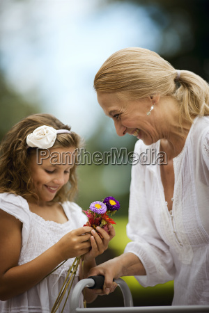 senior woman receiving flowers from her