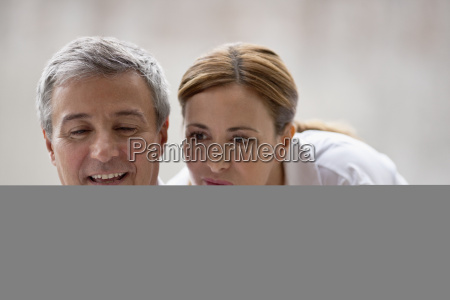 professional couple looking at something on
