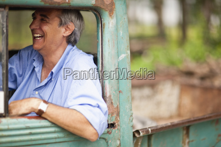 mature man happily sitting in drivers