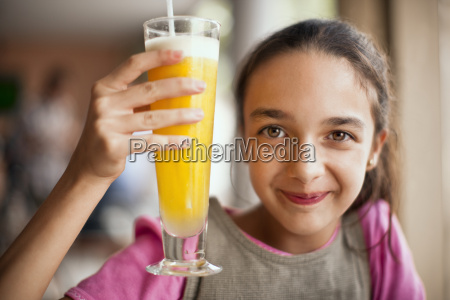 smiling girl holding up tall glass