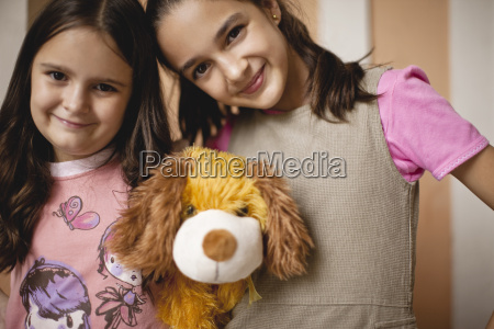 two happy sisters holding soft toy