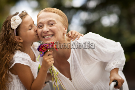 young girl kissing her grandmothers cheek