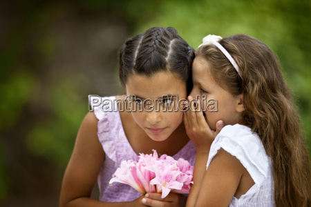 young girl whispering into her sisters
