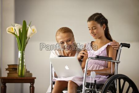 mature woman kneeling beside her granddaughter