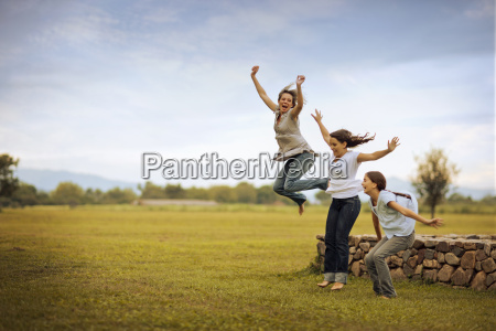 mature woman jumping with her two