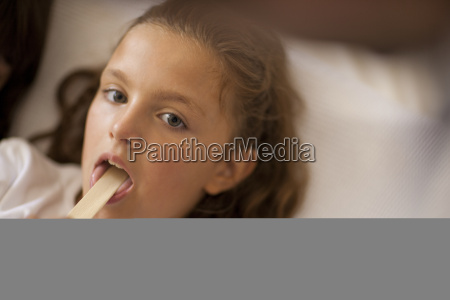 young girl sticking out tongue for