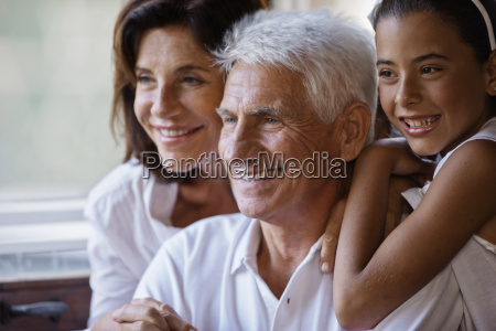 girl sitting happily with her grandparents