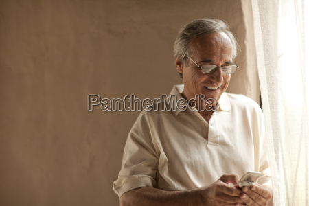 smiling mature man using cell phone