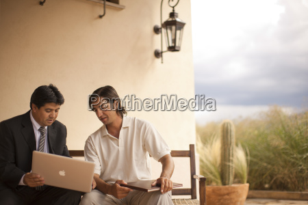 two mid adult men looking at