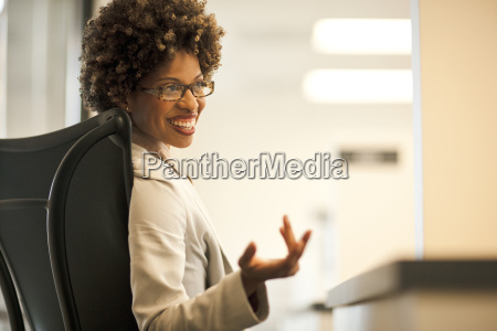 businesswoman sits talking using a hand