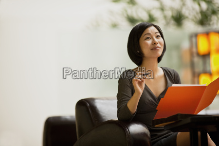 woman sits in a lobby looking