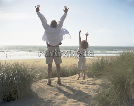 man and his young daughter reaching