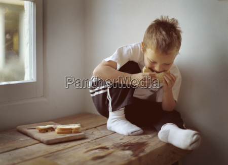 boy eating a pbj sandwich