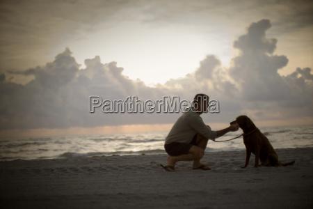 mature adult man patting his dog