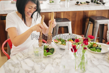 a woman using salad servers to