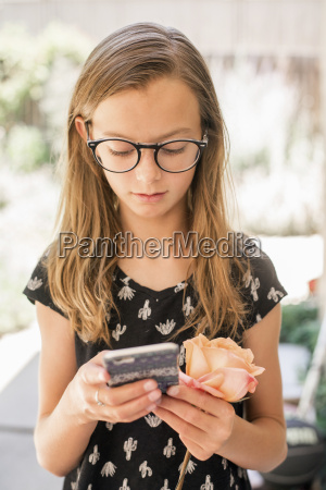 girl with spectacles holding cell phone