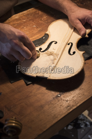 luthier using a mini hand plane