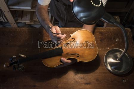 luthier adjusting the sound post of