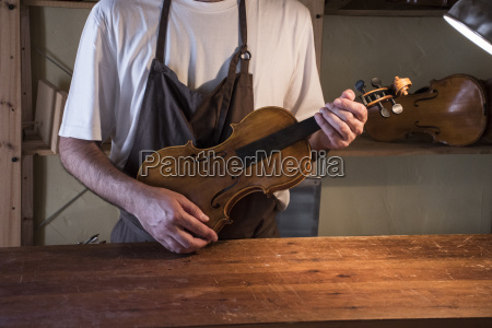 luthier holding a violin in his