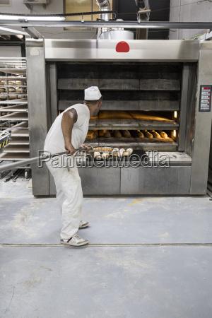 baker taking out freshly baked bread