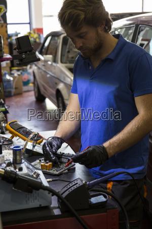 mechanic fixing an electronic car parts