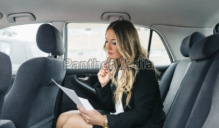 businesswoman working on documents in car