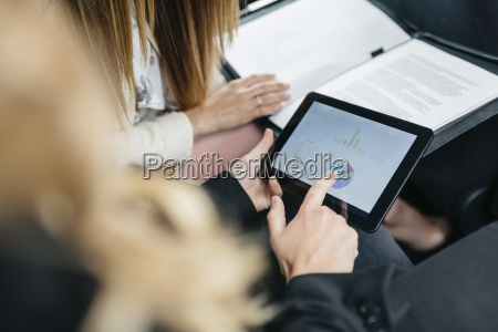 two businesswomen with digital tablet and