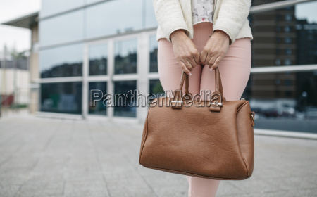 woman holding handbag in front of