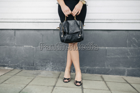 woman holding handbag standing in front