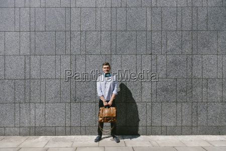 smiling young businessman standing in front
