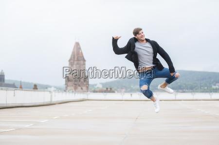 happy young man jumping mid air
