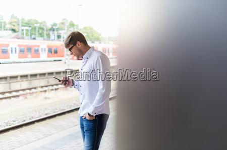 young man at station platform looking