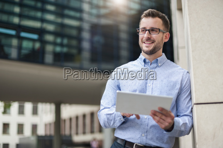 smiling young man with digital tablet