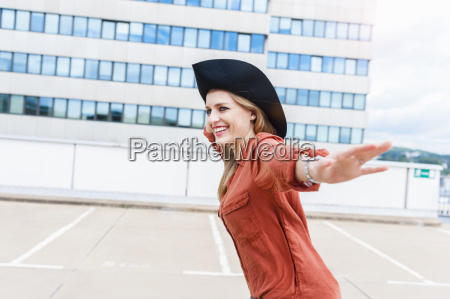 smiling woman with hat on roof
