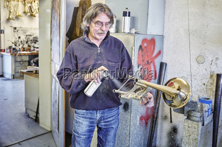 instrument maker using spray can for