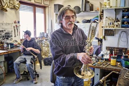 instrument maker examining trumpet in workshop