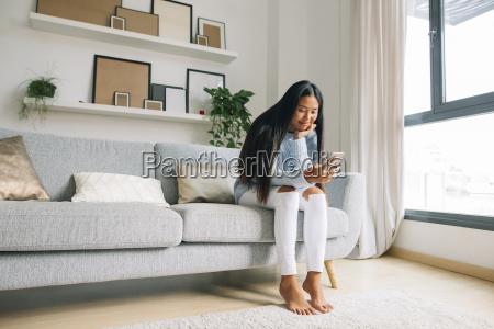 young woman sitting on couch at