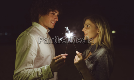 young couple in love holding sparklers