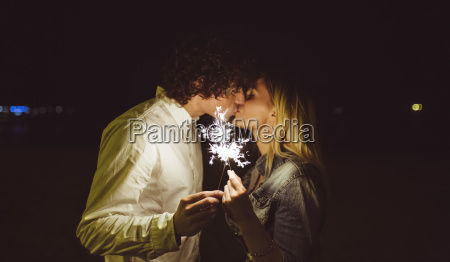 kissing young couple holding sparklers on