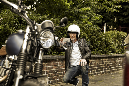 smiling man with motorcycle helmet taking