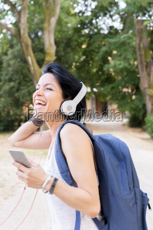 woman listening music with headphones singing