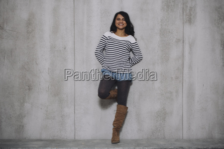 female indian leaning on concrete wall